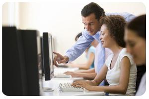 Photo de personnes assises devant des ordinateurs et d'un professeur qui se penche et pointe sur un des écrans.