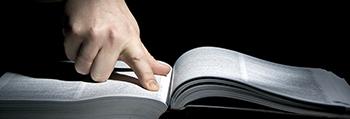 Image d'un doigt qui cherche dans un livre ouvert.