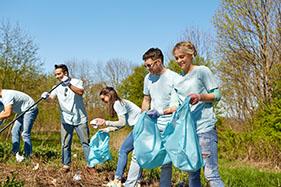 Un groupe de bénévoles a du plaisir à faire le nettoyage d'un parc.